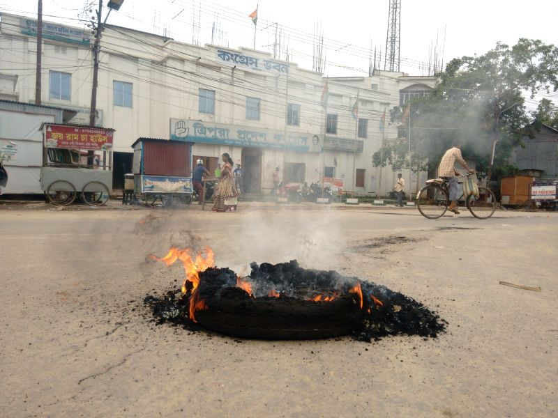 A tyre set on fire during a 24-hour shutdown called by the opposition Congress in support of its 12-point charter of demands, including CBI probe in chit fund activities in Agartala on May ...