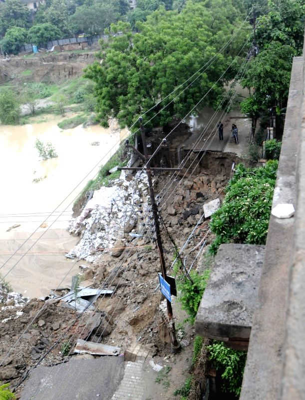 A view of a damaged road at Vasundhara after a part of it caved in during heavy rains, in Ghaziabad on July 26, 2018.