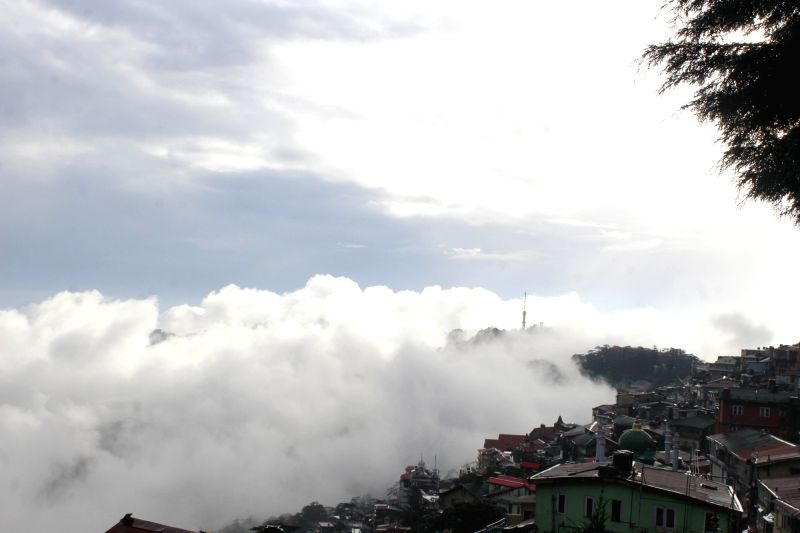 A view of hills covered with fog during sunset in Shimla on July 17, 2016.