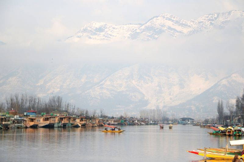 A view of houseboats anchored on the banks of Dal Lake with snow-covered mountains in the backdrop; in Srinagar, on  Feb 2, 2019.