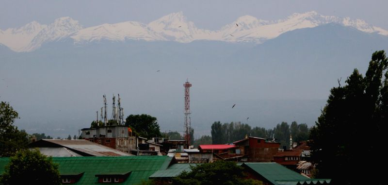 A view of snow clad mountains from Srinagar after fresh snowfalls in Kashmir on June 11, 2017.