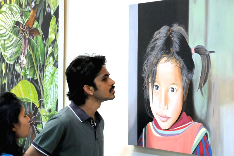 "A visitor during inauguration of ""A few shades of hope"" - a painting exhibition exhibiting Artist Babitha G Nair's creations at Chitrakala Parishath in Bangalore on June 24, 2014. - Babitha G Nai"