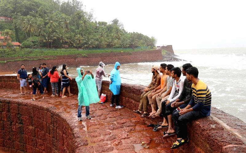"""A visitor poses for selfies despite of a board stating""""Danger, No Selfie Zone"""" put up at Aguada fort in Goa's Sinquerim on July 12, 2018. Amid a spate of drownings and accidents ..."""