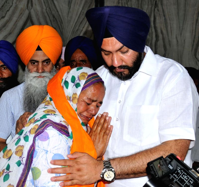 A woman breaks down while offering prayers along with other families and relatives of men stranded in Iraq, at Baba Budha Ji Sahib Gurudwara at Kathunangal in Amritsar on June 21, 2014.