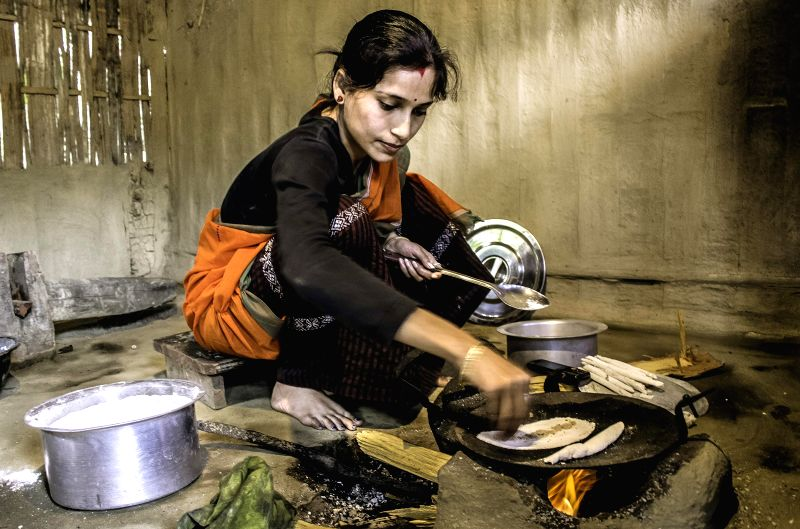 A woman busy cooking `pitha` ahead of the `Bhogali Bihu` at Naharkatia in Tinsukia district of Assam on Saturday.