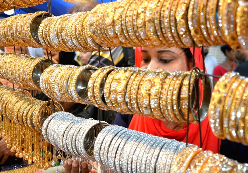 A woman busy shopping at a bangle store ahead of Eid in Kolkata, on Jun 10, 2018.