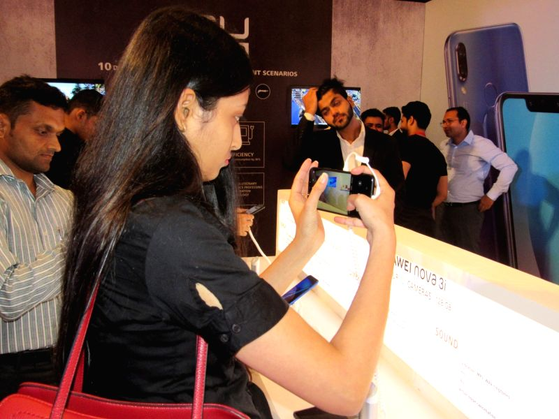A woman checks out the features of a newly launched Nova smartphone, at a launch programme, in New Delhi on July 26, 2018. Huawei Consumer Business Group (CBG) on Thursday brought to India ...