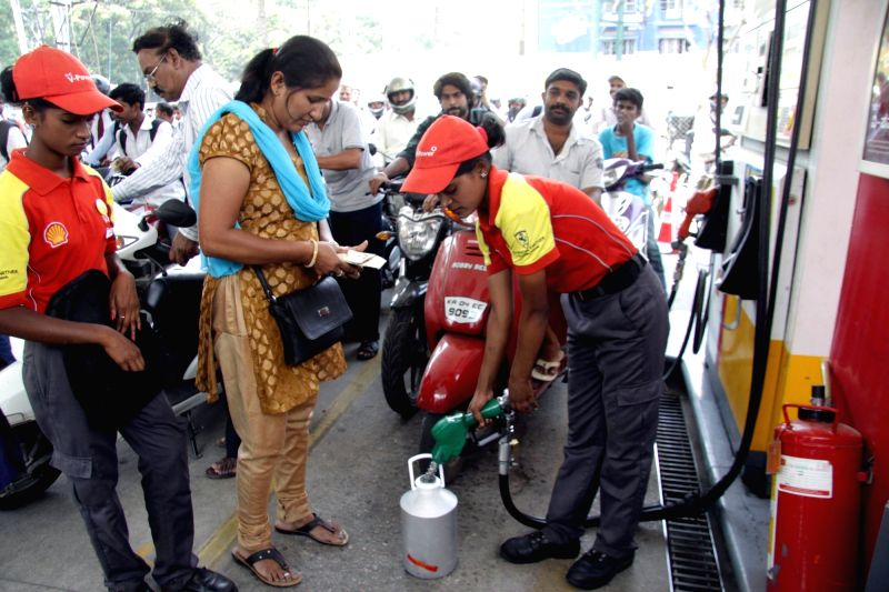 A woman collects petrol from a petrol pump in a container as some petrol pumps were forced to shut down due to short supply in Bengaluru, on April 5, 2016.