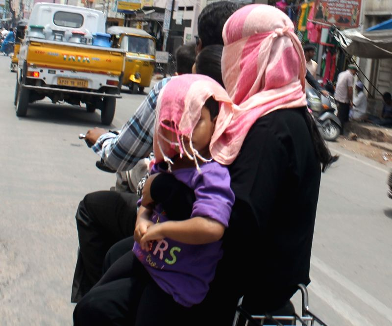 A woman covers her face to shield herself from scorching sun in Hyderabad on May 7, 2014.