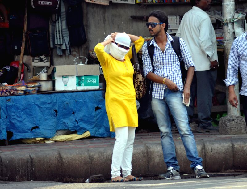 A woman covers herself to avoid direct Sunlight on a hot afternoon in Kolkata on May 15, 2014.
