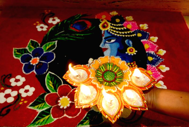 A woman decorates her rangoli with earthen lamps on the eve of Diwali, at her residence in Kolkata.