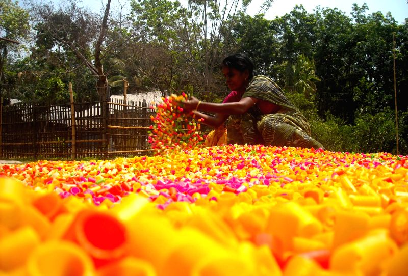 A woman dries papad in sun at a factory located in the outskirts of Agartala on April 28, 2014.