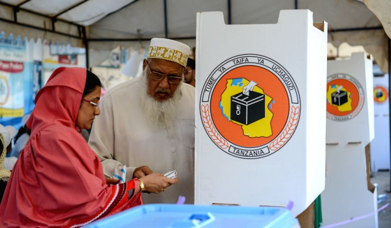 A woman helps a senior write his ballot at a polling station in Dar es Salaam, Tanzania, on Oct. 25, 2015. Around 23 million Tanzanian voters casted their ...