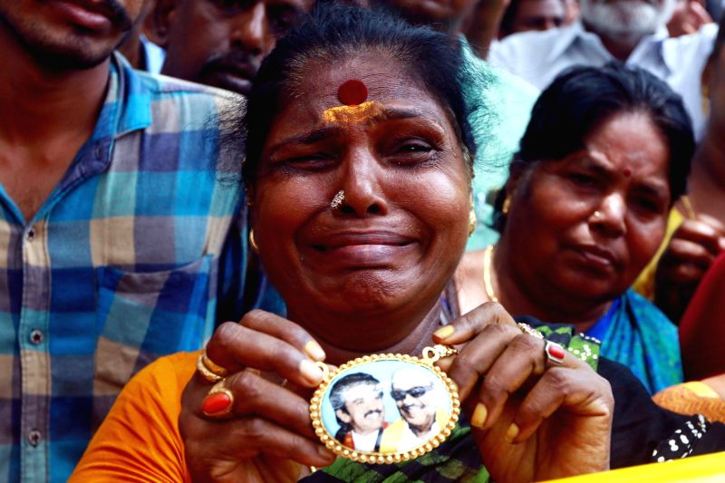 A woman holding pictures of  DMK President M. Karunanidhi and DMK working president M.K. Stalin breaks down outside the Kauvery Hospital where Karunanidhi is admitted, in Chennai, on July ...
