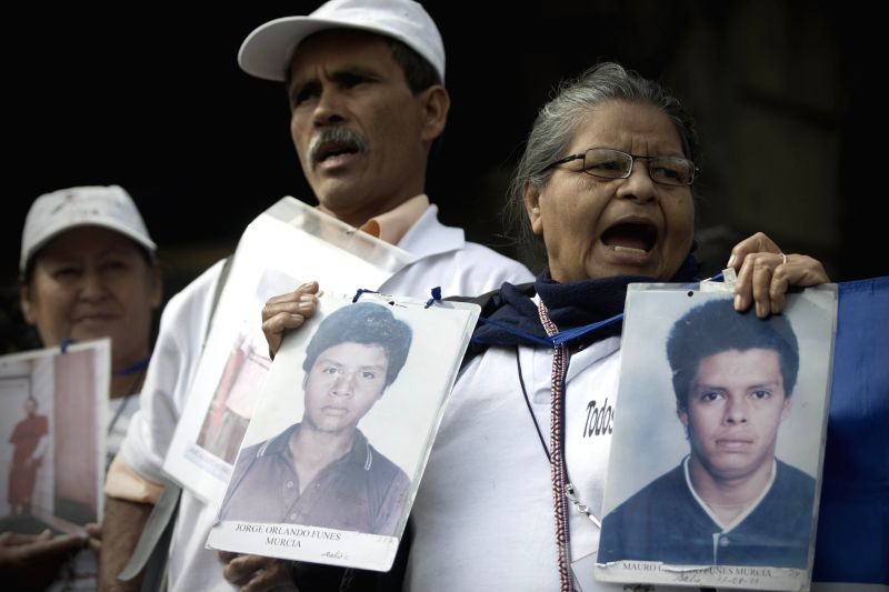 A woman holds images of missing people during an event launched by the caravan of Central American Mothers in Mexico City, capital of Mexico, on Dec. 9, 2015. ...