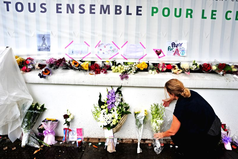 A woman lays flowers outside the French Embassy in Singapore in tribute of the victims of the Paris terrorist attacks, Nov. 16, 2015. Singaporeans mourn for the ...