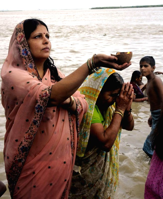 A woman performs rituals on Kali Ghat of Patna on the last Monday of the holy month of Sawan on Aug 4, 2014.