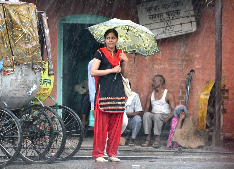 A woman shields herself with an umbrella during rains, in Patna on June 12, 2018.