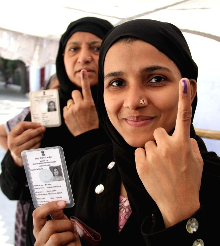 A woman shows her fore finger marked with phosphorous ink after casting her votes at a polling booth during the third phase of 2014 Lok Sabha Polls in New Delhi on April 10, 2014. Elections are being