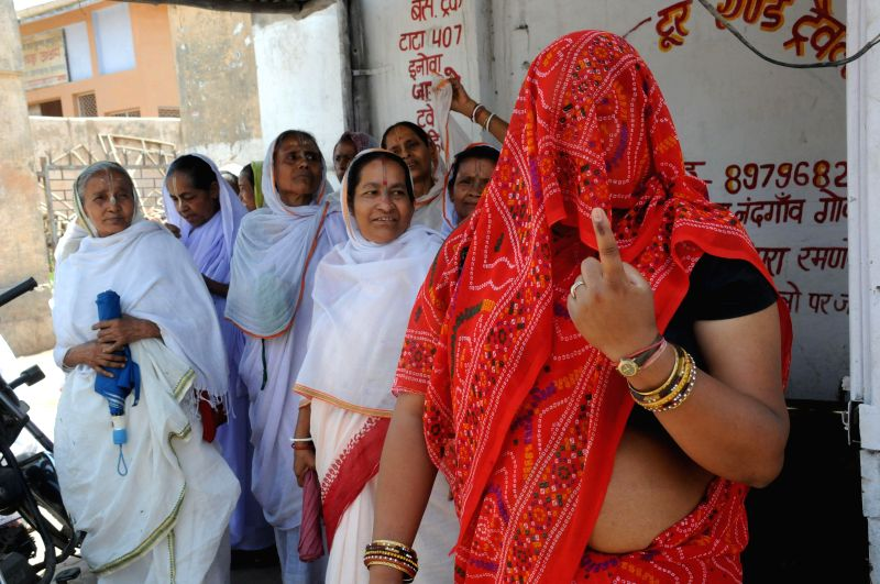 A woman shows her fore finger marked with phosphorous ink after casting her vote at a polling booth during the sixth phase of 2014 Lok Sabha Polls in Vrindavan of Uttar Pradesh's Mathura district on .