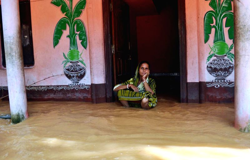 A woman sits on the gate of her flooded home in Jajpur district of Odisha on Aug 5, 2014.