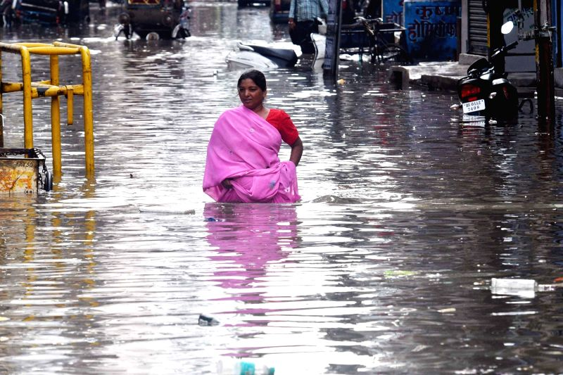 A woman struggles through a water-logged street after heavy rains, in Patna on July 26, 2018.