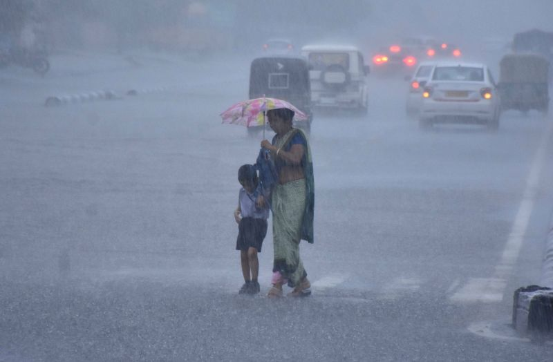 A woman struggles to shield her child using an umbrella as heavy rains lash Jaipur on July 24, 2018.