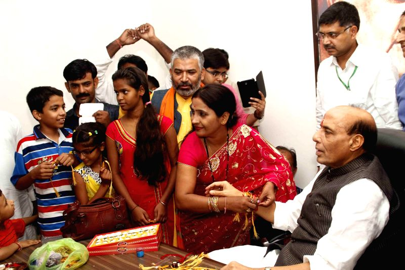 A woman ties a `rakhi` on the wrist of Union Home Minister Rajnath Singh on the occasion of Raksha Bandhan in New Delhi on Aug 10, 2014.