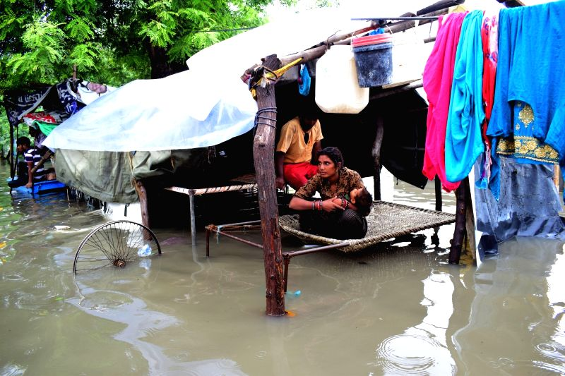 A woman tries to shield her child from the rain water as she sits on cot at a water-logged street, after heavy rains in Mathura on July 26, 2018.
