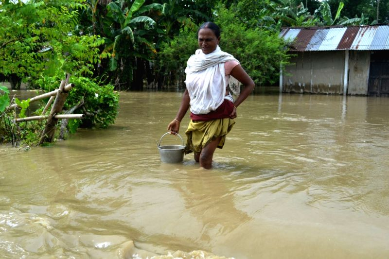 A woman wades through flooded Meleki village in Lakhimpur district of Assam on July 13, 2016.