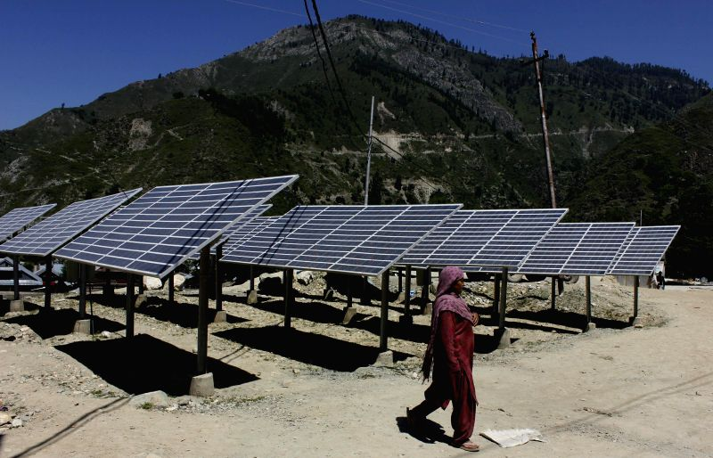 A woman walks past defunct solar panels installed at Sub District Hospital in Tangdar of Jammu and Kashmir  Kupwara district on June 22, 2014.