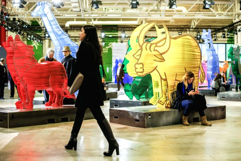 A woman walks past sculptures made of recyclable plastic at the site of the 2015 United Nations Climate Change Conference (COP 21) at Le Bourget on the northern ...