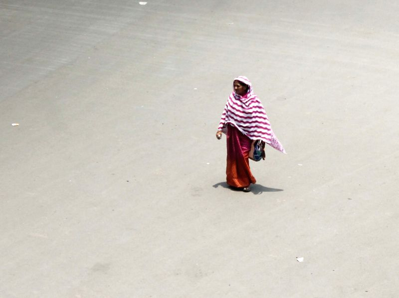 A woman walks through a street on a Zero Shadow Day  - a phenomenon where the Sun is exactly overhead at noon and does not cast a shadow of an object on the ground; in Nagpur on May 26, 2018.