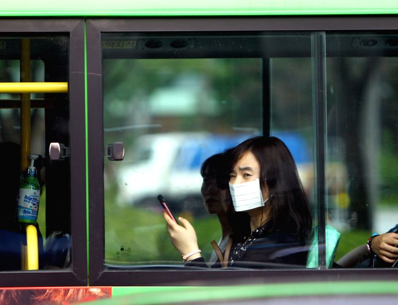 A woman with mask sits in a bus in Seoul, South Korea, June 24, 2015. A Chinese female patient, who was infected with MERS in South Korea, recovered and discharged ...