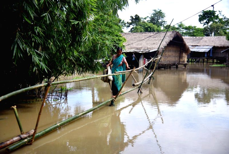 A women use a makeshift bamboo bridge to move across flooded areas of Golaghat District of Assam on Aug 4, 2018.