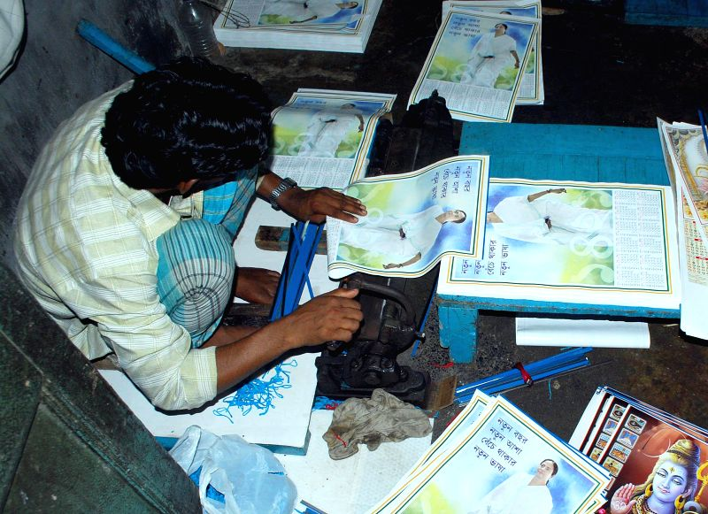 A worker busy making calenders depicting pictures of different political leaders at a workshop in Kolkata on April 11, 2014.