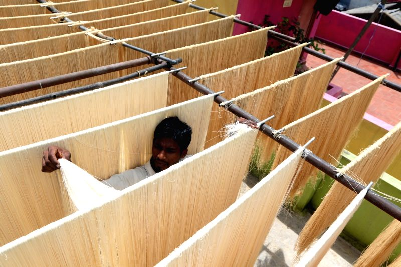 A worker dries strands of vermicelli, used to prepare various sweet dishes consumed during the Muslim holy month of Ramadan, at a vermicelli manufacturing unit in Chennai on June 9, 2018.