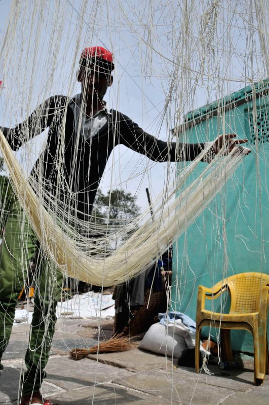 A worker hangs strands of vermicelli to dry in sun at a workshop during the holy month of Ramadan in Hyderabad on July 4, 2014.