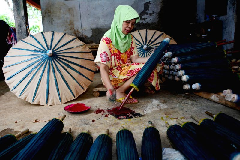 A worker paints paper umbrellas at Banyumas, Central Java, Indonesia, Nov. 27, 2015.