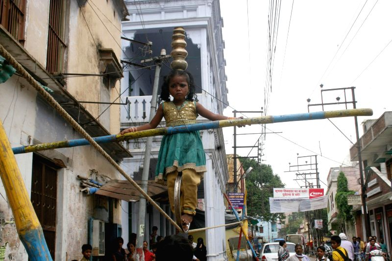 A young funambulist shows her skills on a Varanasi street on Aug 26, 2014.