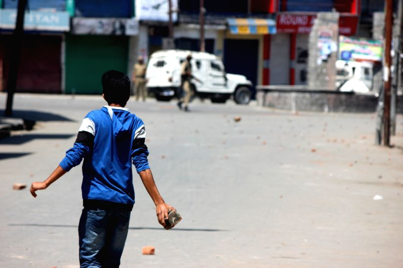 A youth hurls a stone towards security personnel in Anantnag of Jammu and Kashmir on June 3, 2017.