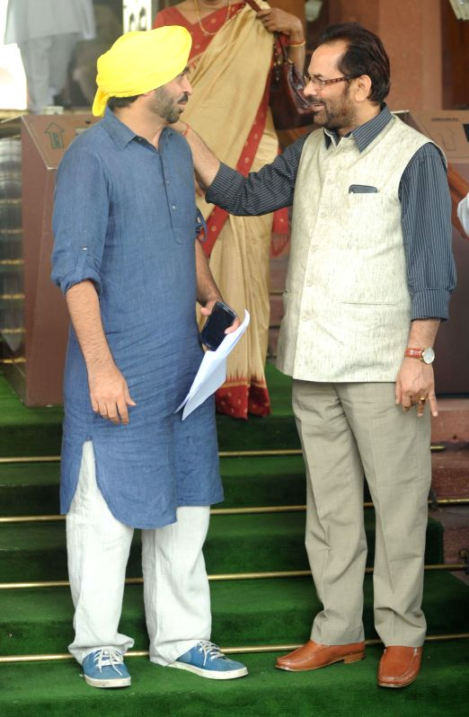Aam Aadmi Party (AAP) MP from Sangrur, Bhagwant Mann with BJP MP Mukhtar Abbas Naqvi at the Parliament on Aug 5, 2014.