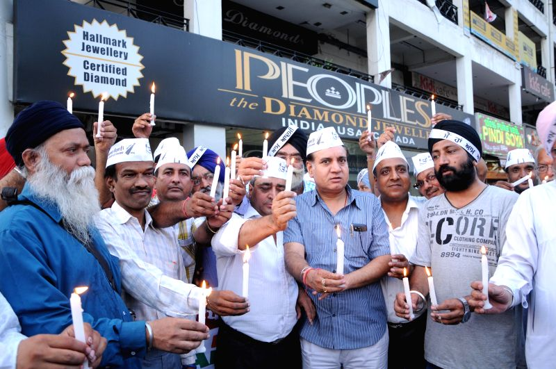 Aam Aadmi Party (AAP) workers participate in a candlelight vigil organised to pray for the safety of Indian nationals trapped in violence hit Iraq in Amritsar on June 22, 2014.