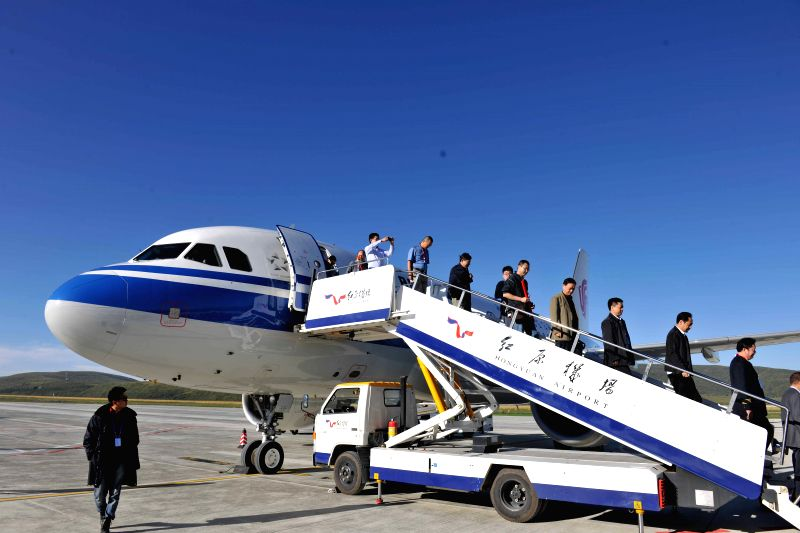Passengers walk down from the first aircraft arriving at the Hongyuan Airport in Hongyuan County of Aba Prefecture, southwest China's Sichuan Province, Aug. 28, 2014. ..