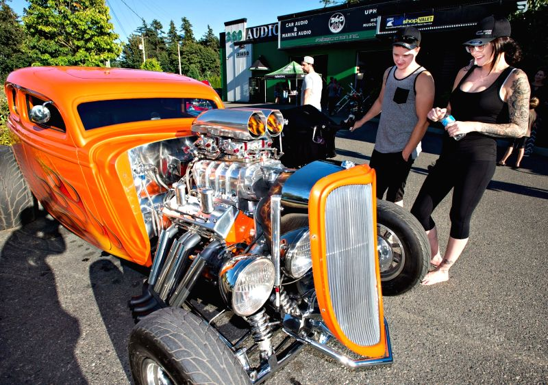 ABBOTSFORD, July 13, 2018 - People look at a classic restored car during the community car show hosted by garages in Abbotsford, Canada, July 12, 2018.
