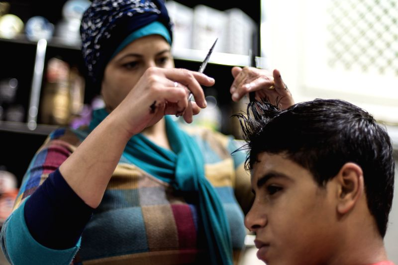 Abeer Mahmoud, 43, an Egyptian female barber, cuts hair for a man at the barbershop she owns in the Nasr City of Cairo, Egypt, on Dec. 10, 2015. Abeer Mahmoud, who has been working as an ...
