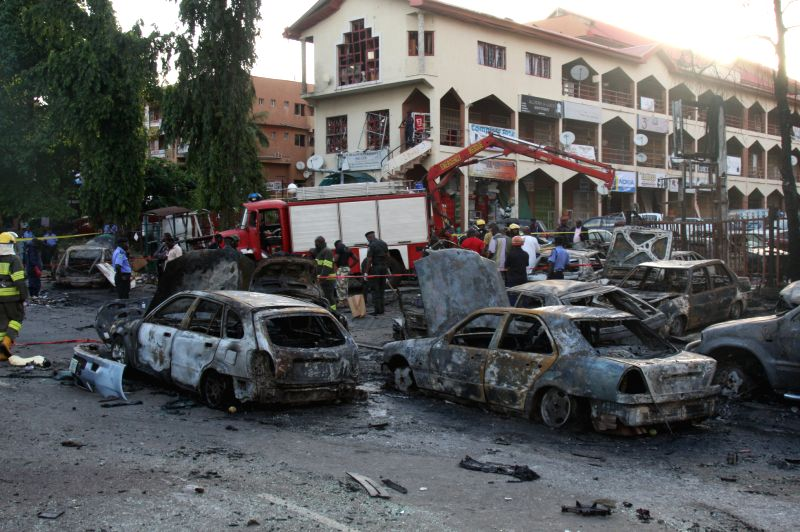 Damaged cars are seen at the site of a bomb explosion in the central business area in Nigeria's capital Abuja, on June 25, 2014. At least 19 people have been killed ..