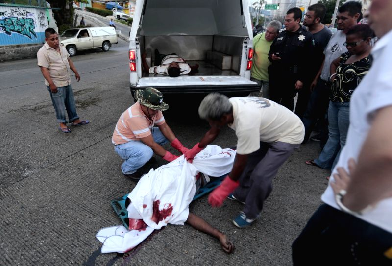 People move the body of a man murdered along with his companion by alleged armed men at a street of Acapulco City, in south Mexico, on July 11, 2014. According to .
