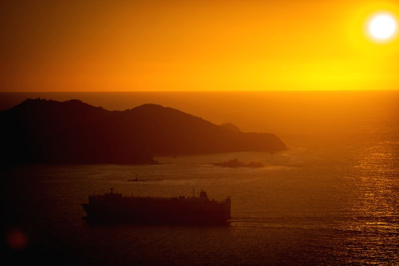 A boat sails during the sunset in the Acapulco Port Bay, in Acapulco, Mexico, on March 23, 2015.