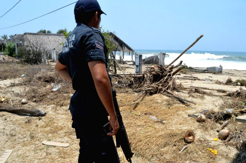A policeman watches the debris after a large ocean swell at a beach in Acapulco, Guerrero state, Mexico, on May 3, 2015. (Xinhua/Adriana Covarrubias/NOTIMEX) (dadjj))